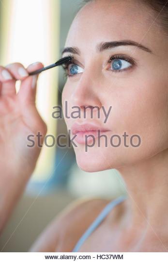 Mid adult woman applying mascara. - Stock Image