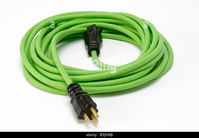A coiled green electrical extension power cord with two plugs - Stock Image