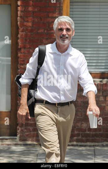 Businessman walking down street with coffee - Stock-Bilder