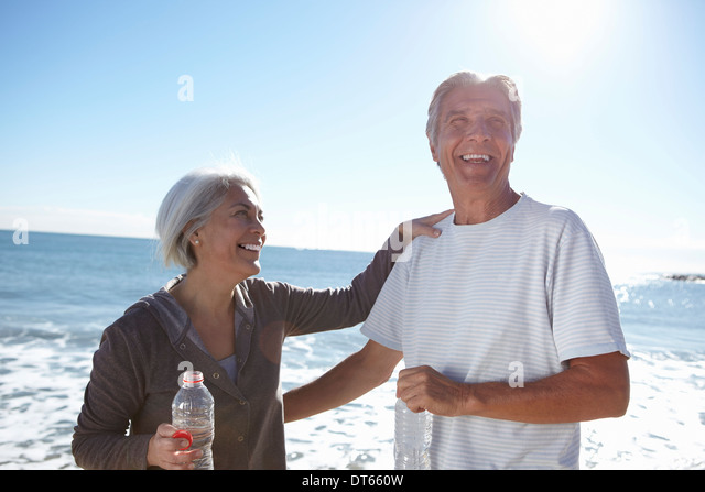 Portrait of happy couple by seaside - Stock Image
