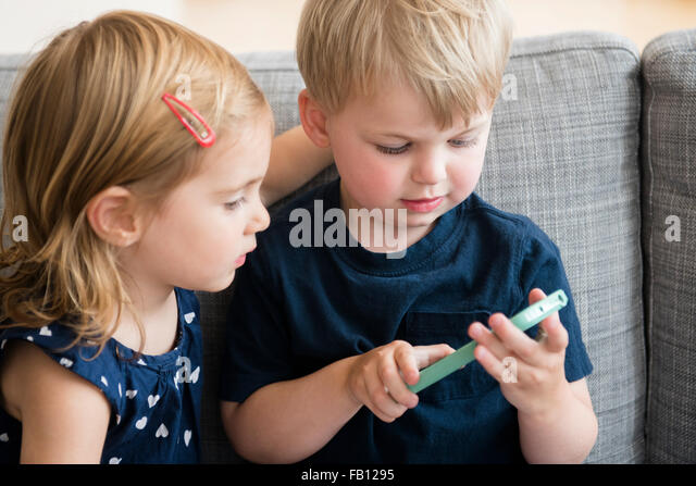 Brother with sister (2-3) playing with smart phone - Stock Image
