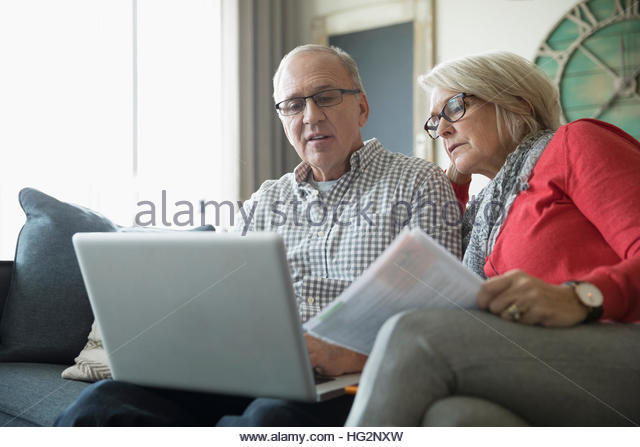 Senior couple with paperwork using laptop on living room sofa - Stock Image
