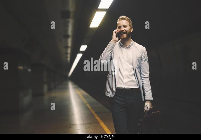 Businessman waiting for subway in underground station - Stock Image
