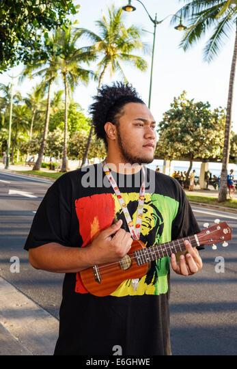 Hawaii Hawaiian Honolulu Waikiki Beach Kalakaua Avenue man playing ukulele - Stock Image