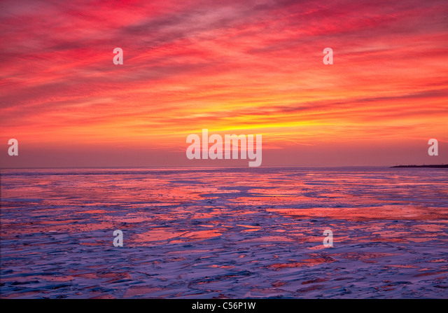 The Netherlands, Oosterdijk, Winter, snow, view on frozen lake called IJsselmeer. Sunrise. - Stock-Bilder