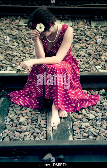 a sad girl on railway tracks - Stock Image