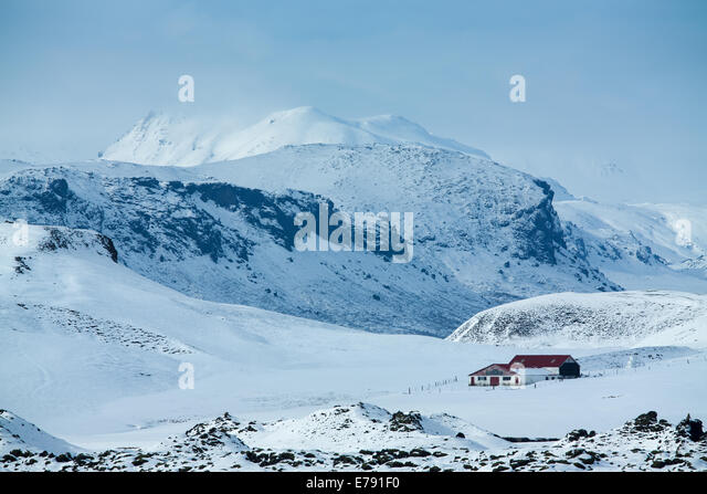 an isolated farmhouse in the snow with the mass of Katla beyond, southern Iceland - Stock Image