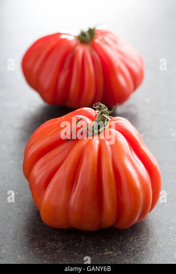 Coeur De Boeuf. Beefsteak tomatoes on old kitchen table. - Stock Image