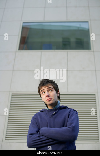 Shy young man looking up - Stock Image