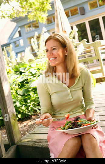 Close-up of a mid adult woman eating vegetable salad and smiling - Stock-Bilder