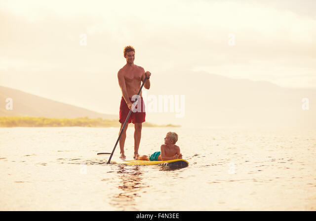 Father and son stand up paddling at sunrise, Summer fun outdoor lifestyle - Stock-Bilder