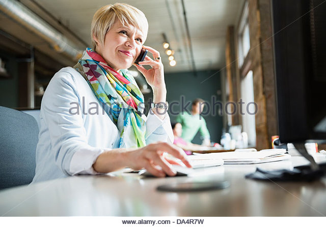 Female entrepreneur using mobile phone at desk - Stock-Bilder