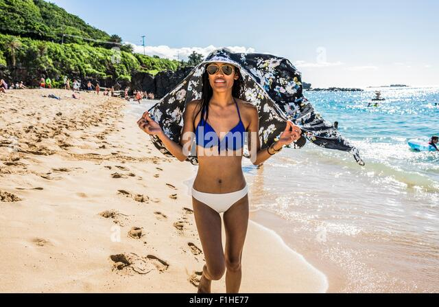 Young woman wearing bikini holding scarf over her head on  Waimea Beach, Oahu, Hawaii, USA - Stock Image