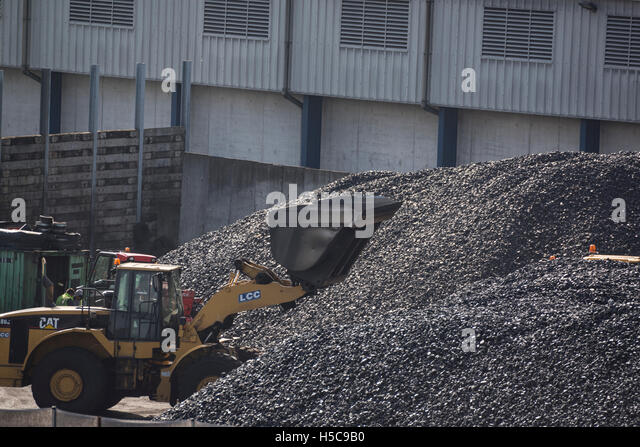 A pile of coal with a digger in belfast port - Stock Image
