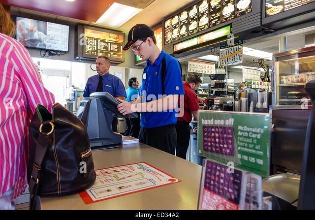 Illinois Gibson City McDonald's fast food restaurant counter man employee working job uniform order order taker - Stock Image