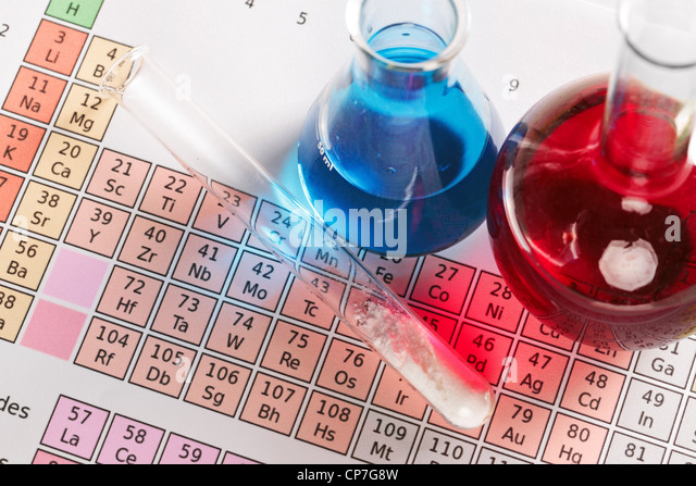 Photo of a periodic table of the elements with flasks and test tube containing chemicals both liquid and powder. - Stock Image