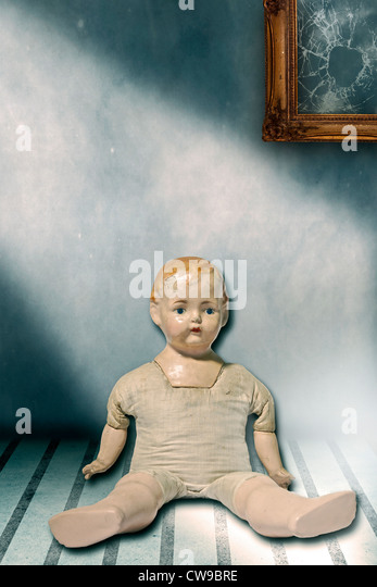 an old doll sitting in a shabby room - Stock Image