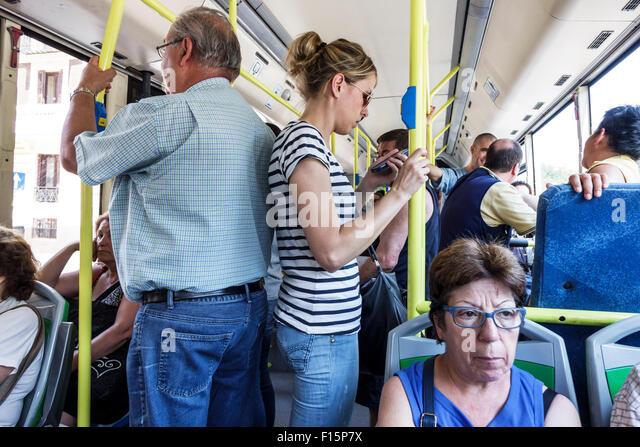 Madrid Spain Europe Spanish Metro EMT bus public transportation riders passengers standing Hispanic man woman - Stock Image