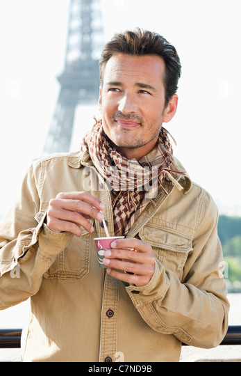 Man holding a disposable cup with the Eiffel Tower in the background, Paris, Ile-de-France, France - Stock Image