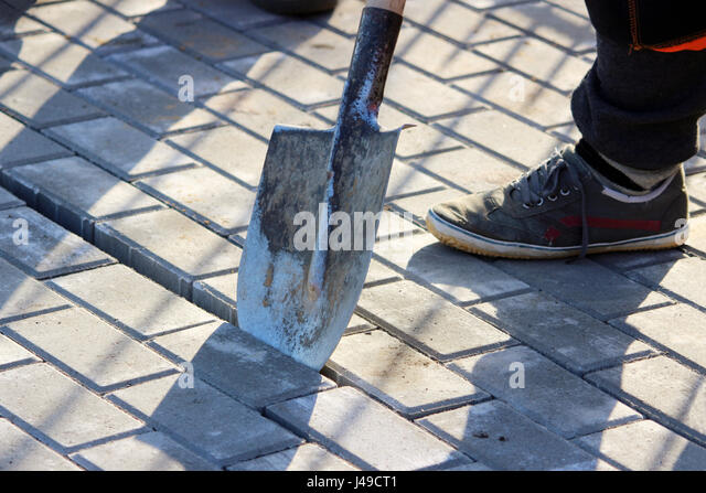 Repair of the sidewalk. The working mason with the help of a shovel decides how to fix the wrongly laid paving slab. - Stock Image