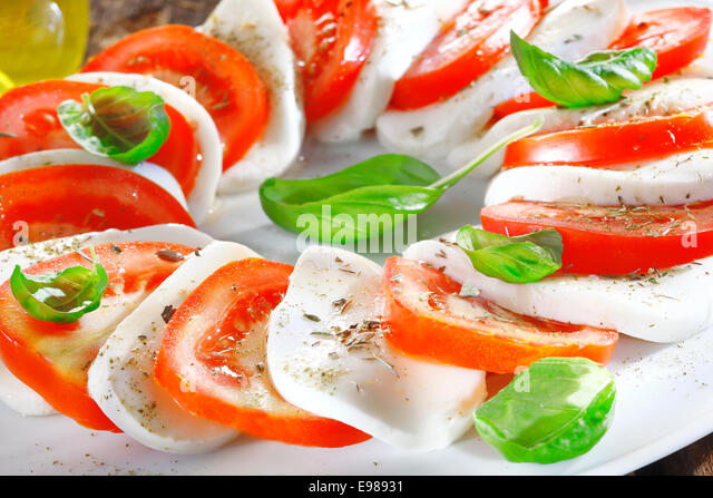 Artistically arranged cheese and tomato salad in alternating slices of red and white garnished with fresh herbs - Stock-Bilder
