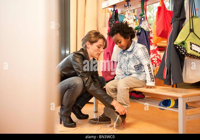 Kindergarten teacher helping boy getting dressed - Stock Image
