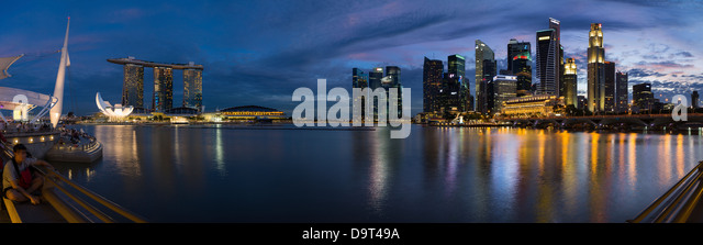 the skyline at night from the Esplanade with Marina Bay (left) and the Central Business District (right), Singapore - Stock Image