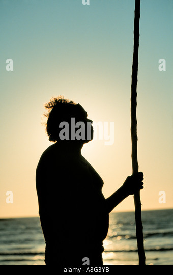 aboriginal with walking stick gazing at the sea, Darwin, Australia - Stock Image