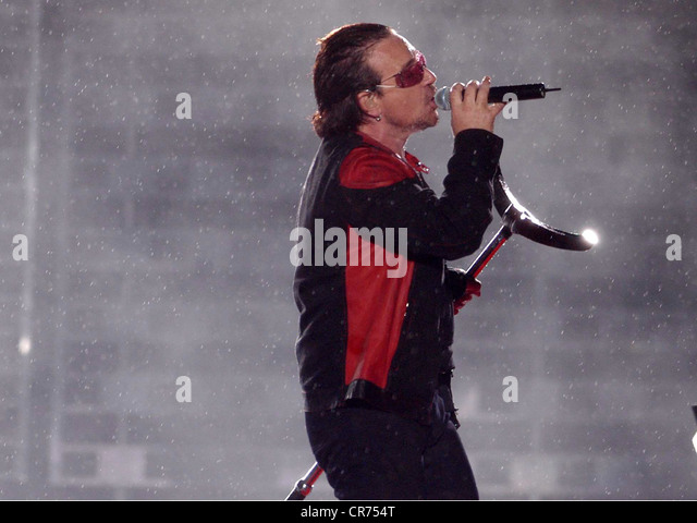 U2, Irish rock band, frontman Bono Vox is singing in the rain, half length, Olympic stadium, Munich, Germany, 2.8.2005, - Stock Image