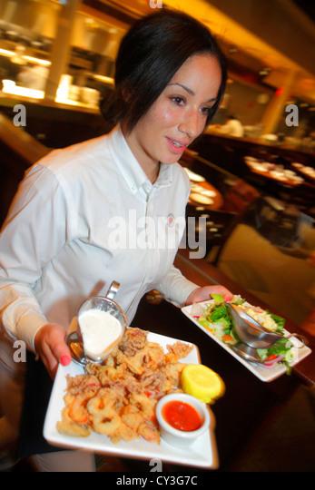 Boston Massachusetts Newbury Street Joe's American Bar & Grill waitress woman job serving plates food clam - Stock Image
