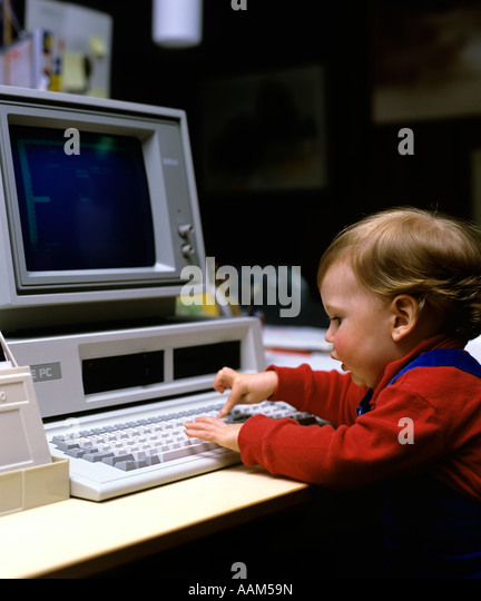 1980s YOUNG CHILD BOY GIRL PLAYING WITH EARLY IBM PC COMPUTER PRESSING KEY ON KEYBOARD - Stock Image
