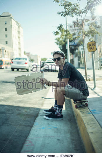 Young man sitting on kerb holding hitchhiking sign - Stock-Bilder