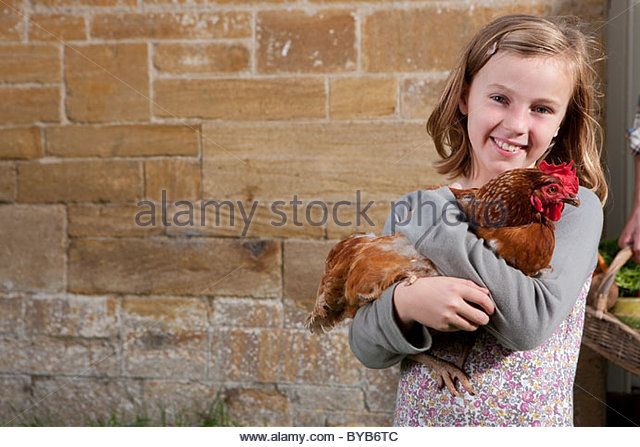 Smiling girl holding pet chicken - Stock Image