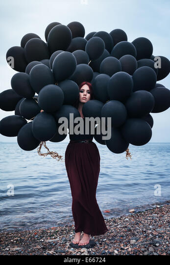 Beautiful girl walking with black balloons - Stock Image