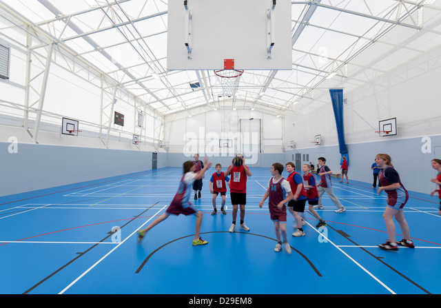 children palying basketball inside school sports hall - Stock Image