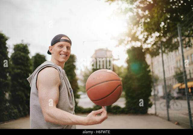 Portrait of smiling streetball player spinning the ball on outdoor court. Happy young man balancing basketball on - Stock Image