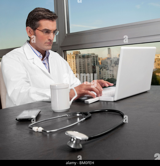 Doctor working on a laptop - Stock Image