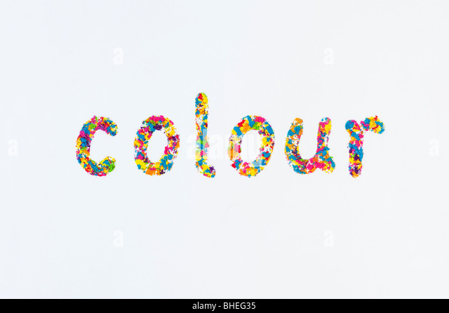 The word COLOUR (English spelling) , spelt using multi coloured powder on white background - Stock Image