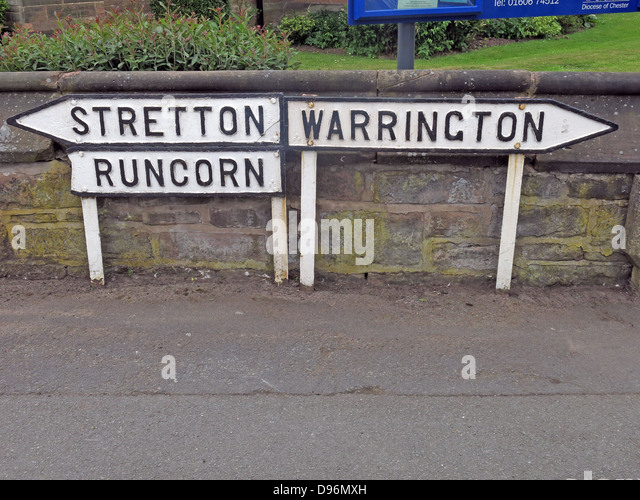 Old fashioned black on white cast iron signposts to Stretton , Runcorn and Warrington at Appleton Thorn Cheshire - Stock Image