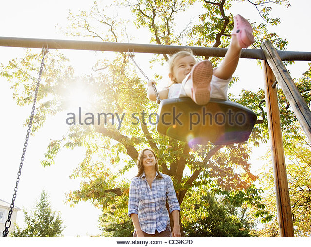 Mother pushing daughter on swing in sunny park - Stock-Bilder