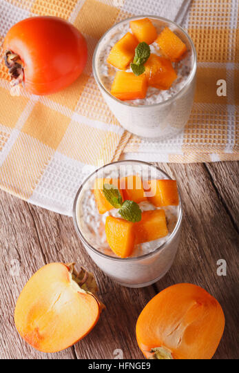 Yogurt with chia seeds and persimmon on the table. vertical top view - Stock Image