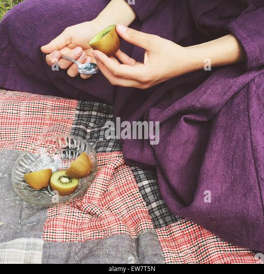 Close-up of a woman eating a kiwi fruit - Stock Image
