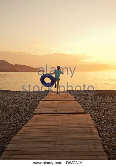 Boy running on boardwalk, Fethiye, Turkey - Stock Image