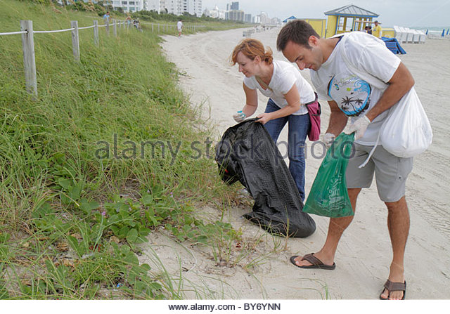 Miami Beach Florida Coastal Cleanup Day volunteer litter trash pollution public beach pick up man woman couple - Stock Image