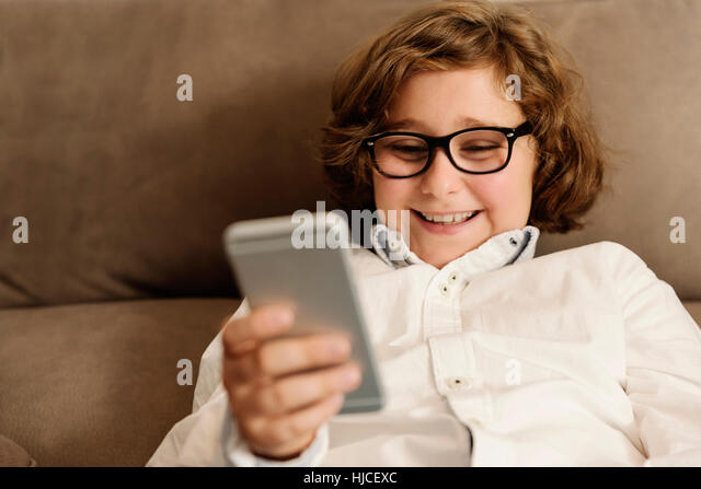 Child boy using his mobile phone at home. - Stock Image