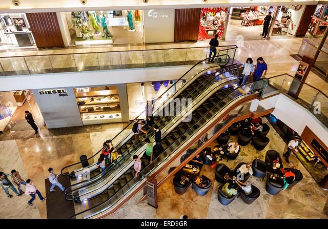 Mumbai India Asian Lower Parel High Street Phoenix mall inside interior Palladium shopping escalators Diesel - Stock Image