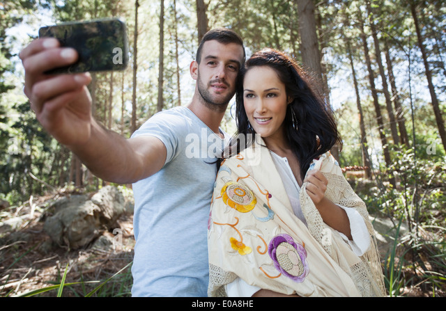 Young couple taking self portrait photograph in forest - Stock-Bilder