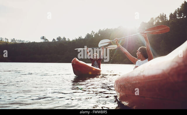 Happy young couple enjoying canoeing on summer day. Young man and woman having fun during kayaking. - Stock Image
