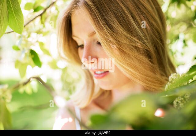 MODEL RELEASED. Young woman with blonde hair and leaves. - Stock-Bilder