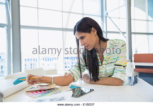 Creative businesswoman looking at color swatches in office - Stock Image